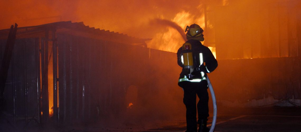 Firefighter spraying burning home with Idaho Falls fire damage